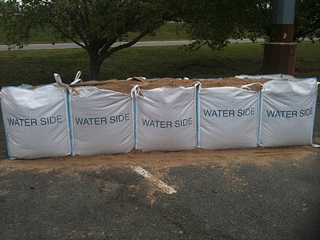 Filled flood barrier set up in parking lot